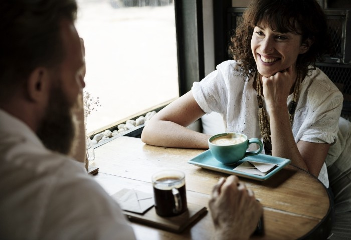 man and woman talking at cafe - conversation etiquette